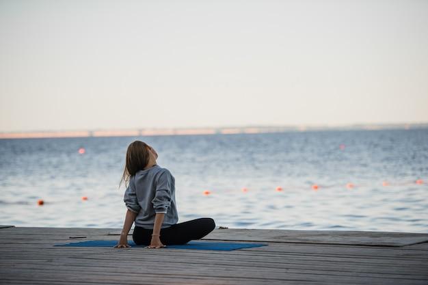 Morgenaufnahme eines mädchens in lotussitz, das stretching-yoga-übungen auf dem pier macht