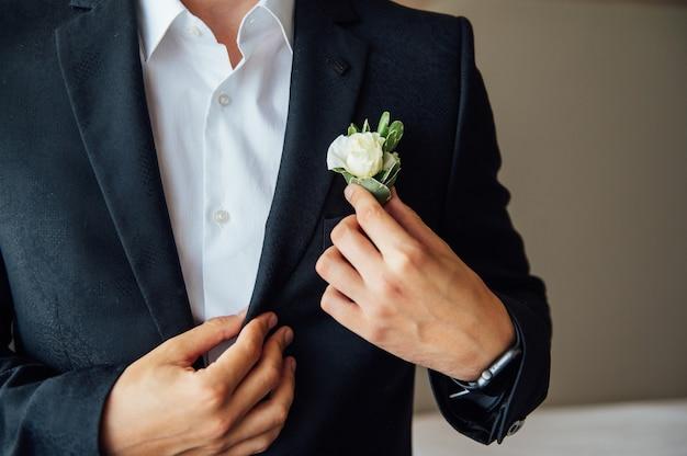 Morgenbräutigam, bräutigam in einer jacke, der bräutigam richtet das knopfloch gerade, hochzeitstag
