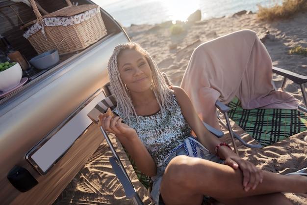 Morgencroissant. netter stilvoller ansprechender reisender mit weißen dreadlocks, die morgencroissant essen