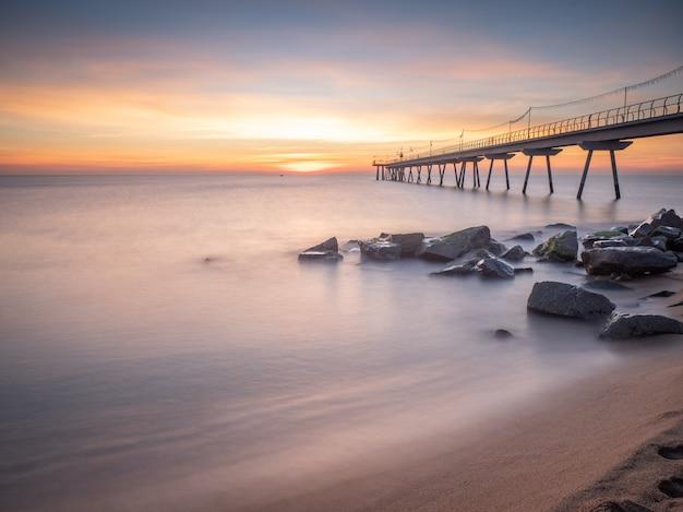 Morgendämmerung am strand mit alten ölbrücke, seideneffekt - (pont del petroli, badalona, spanien)