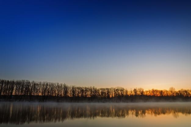 Morgendämmerung über der glatten oberfläche des frühlingsflusses.