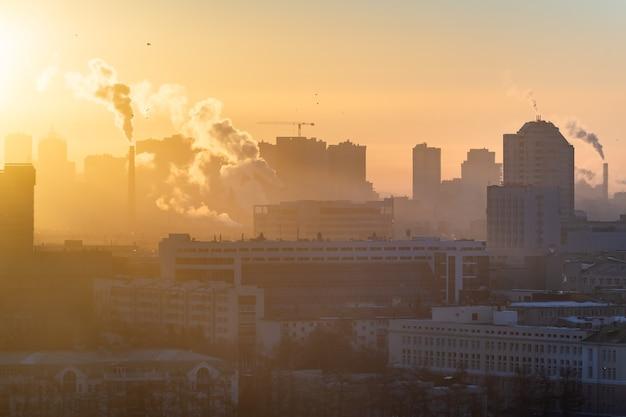 Morgendämmerung über der stadt. die sonne beleuchtet den smog über der stadt