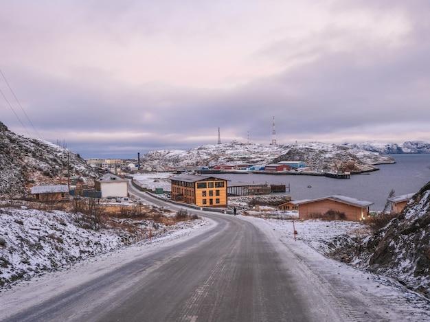 Morgendämmerungswinteransicht des kleinen küstenfischerdorfes teriberka im norden der kola-halbinsel. eine autobahn in den arktischen hügeln. russland.