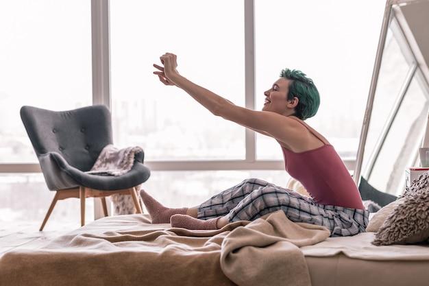 Morgendliche dehnung. glückliche frau im schlafanzug, die ihren körper beim aufwachen am morgen ausdehnt
