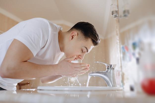 Morgendliche hygiene, der junge wird in einem waschbecken mit wasserspray gewaschen