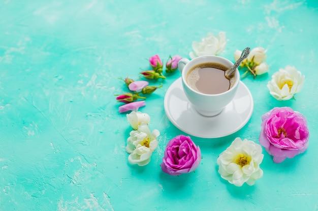 Morgendliche tasse kaffee und frische schöne rosa und weiße rosenblumen, flache anordnung, kopierraum. kaffeegetränkekonzept mit tasse americano und rosen auf betonwand. morgen weibliche wand