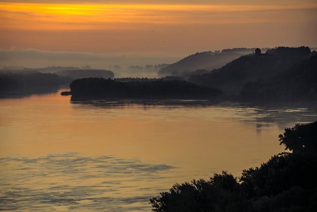 Morgendunst über dem tal des flusses. gold leuchtet von der morgendämmerung am himmel und reflex auf dem wasser. vögel fliegen im himmel bei sonnenaufgang. nebel am flussufer mit wald.