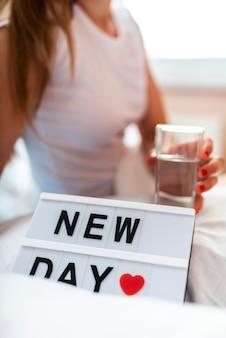 Morgenfrau, die ein glas wasser anhält