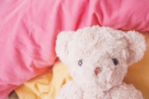 Morgenfrisch liegt der teddybär auf dem bett, er fühlt sich erfrischt und voll.