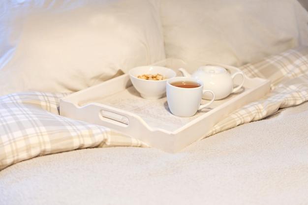 Morgenfrühstück am bett gestreiftes teeset auf frühstückstablett im schlafzimmer