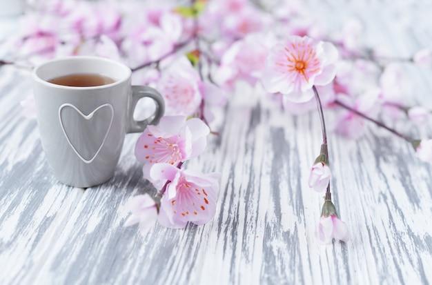 Morgenfrühstück des tees in einer schale mit einem herzen mit rosa blumen