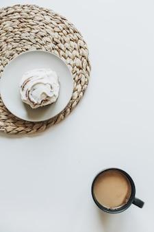 Morgenfrühstück mit kaffee mit milch und kuchen auf weißem tisch.