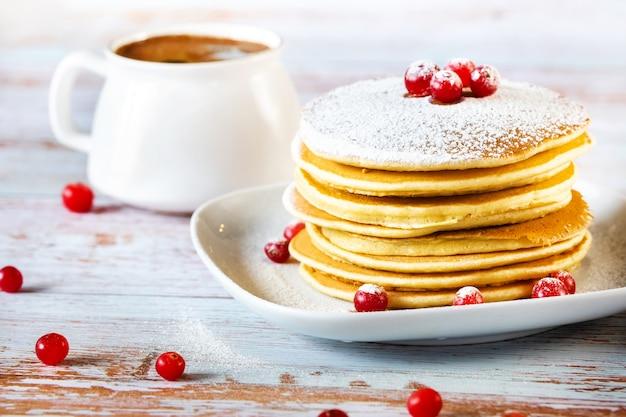 Morgenfrühstück mit pfannkuchen mit preiselbeeren und puderzucker auf einem holztisch und einer tasse kaffee