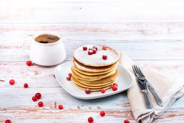 Morgenfrühstück mit pfannkuchen mit preiselbeeren und puderzucker auf einem holztisch und einer tasse kaffee.