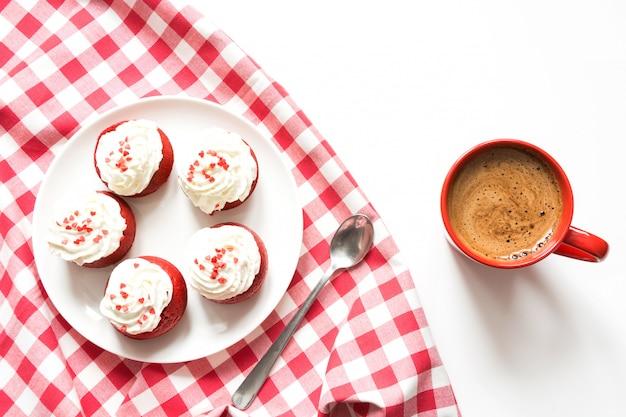 Morgenfrühstück mit schale schwarzem kaffee und fünf roten samtkleinen kuchen auf weiß. ansicht von oben.