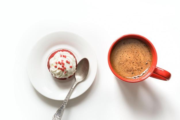 Morgenfrühstück mit schale schwarzem kaffee und rotem samtkleinem kuchen auf weiß. ansicht von oben.