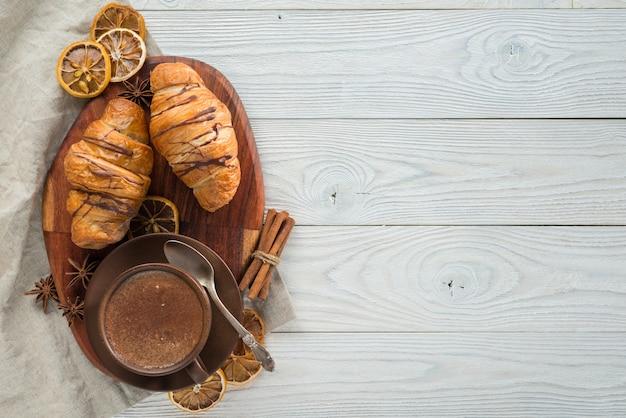 Morgenfrühstück, zusammensetzung von kaffee und croissants auf einem hölzernen hintergrund