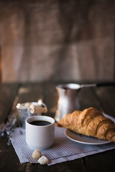 Morgenfrühstückskaffee und -hörnchen auf kopienraumhintergrund