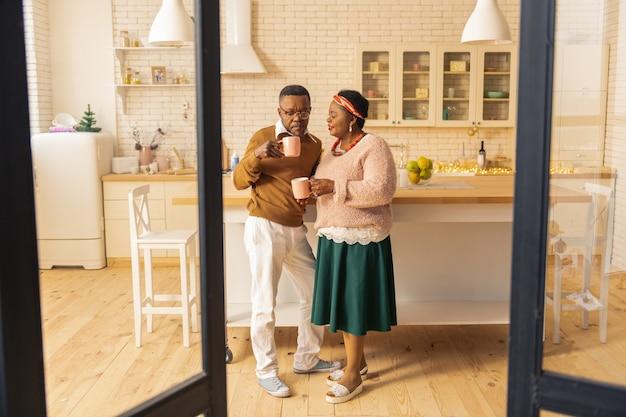Morgengetränk. nettes ehepaar, das morgens beim kaffeetrinken in der küche steht