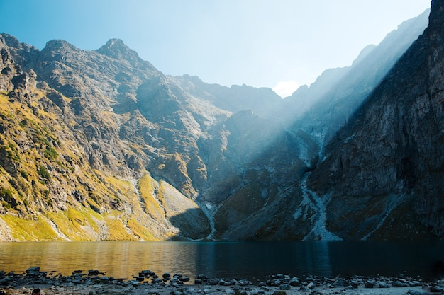 Morgenhimmel mit sonnenlicht über felsigen tatra-bergen in der nähe des morskie oko-sees