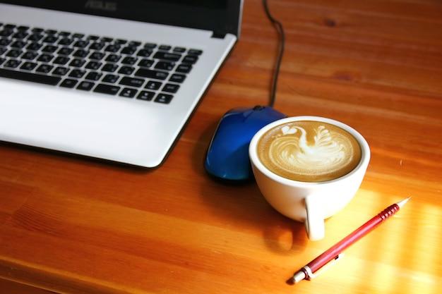 Morgenkaffee auf dem arbeitstisch. licht und schatten auf weißer kaffeetasse auf holzboden mit unscharfem laptop-hintergrund