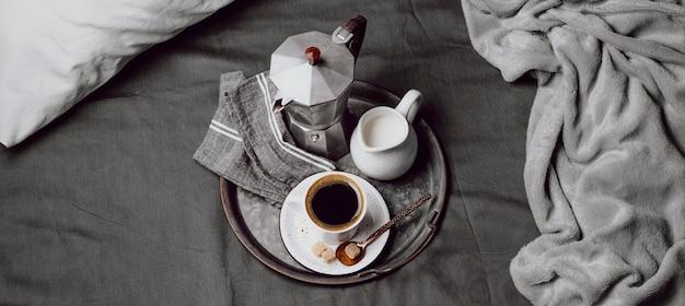 Morgenkaffee auf dem bett mit milch und wasserkocher