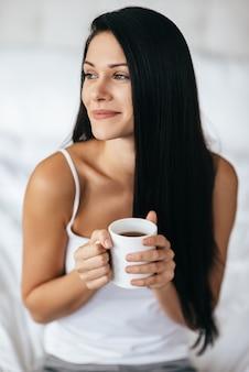 Morgenkaffee genießen. attraktive junge frau, die eine tasse hält und wegschaut