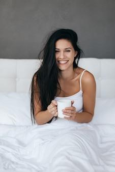 Morgenkaffee genießen. attraktive junge frau, die eine tasse lächelt und hält