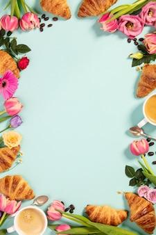 Morgenkaffee, hörnchen und schöne blumen. flach liegen