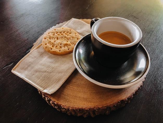 Morgenkaffee in der schwarzen schale und in den plätzchen auf hölzernem schneidebrett