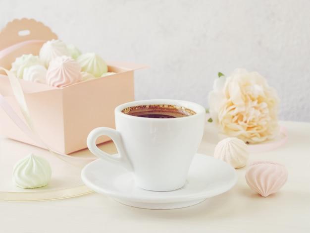 Morgenkaffee mit einem notizbuch und einem kasten füllte mit kleinen meringen auf einem hölzernen hellen hintergrund