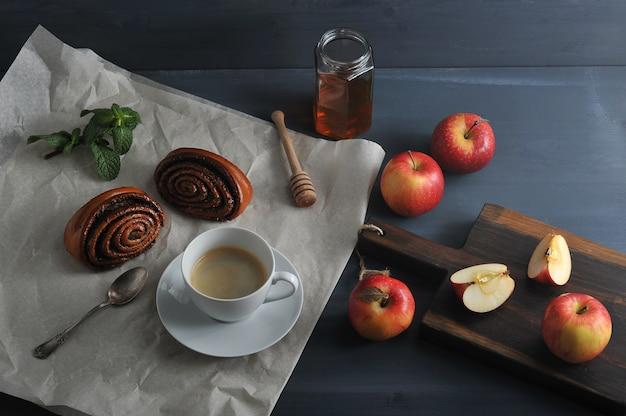 Morgenkaffee mit kaffee und brötchen mit mohn, äpfeln und honig