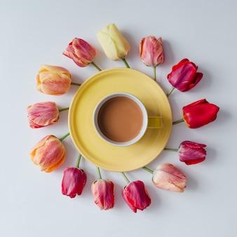 Morgenkaffee mit kreativer anordnung der tulpenblumen an der hellen wand. flach liegen.