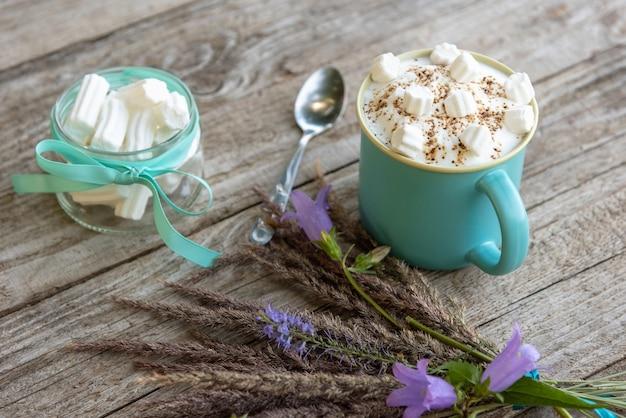 Morgenkaffee mit schaum und marshmallows mit blumen auf dem tisch.