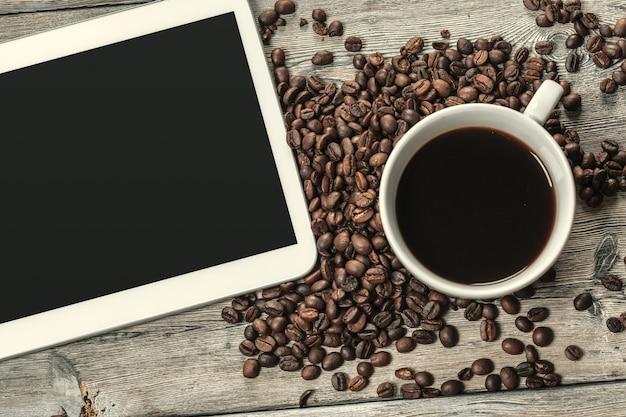 Morgenkaffeetasse mit einer digitalen tablette für geschäftsarbeit