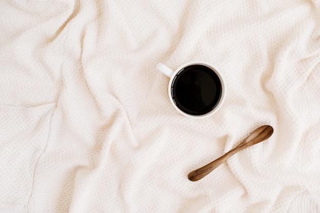 Morgenkaffeetasse mit holzlöffel auf beige textilhintergrund. flache lage, ansicht von oben
