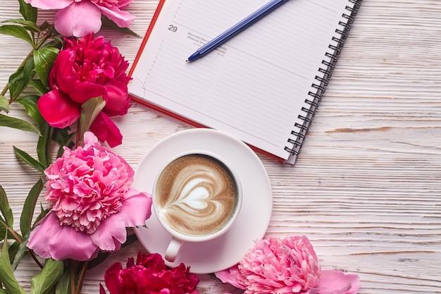 Morgenkaffeetasse zum frühstück, leeres notizbuch, bleistift und rosa pfingstrosenblumen auf weißer steintischoberansicht im flachen laienstil.