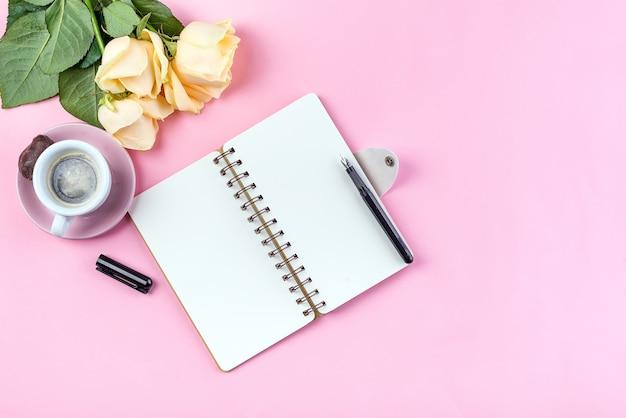 Morgenkaffeetasse zum frühstück, leeres notizbuch, bleistift und stieg auf rosa tischplatteansicht