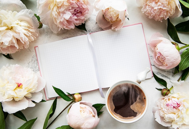 Morgenkaffeetasse zum frühstück, leeres notizbuch und rosa pfingstrosenblumen auf weißem steinhintergrund, draufsicht im flachen laienstil.