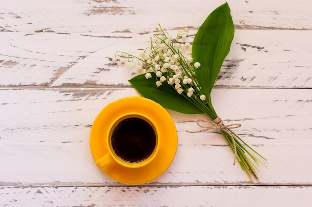 Morgenkaffeetischdekoration mit maiglöckchenblumenstrauß. gelbe tasse mit schwarzem kaffee verzierte frühlingsblumen auf holztisch, draufsicht.
