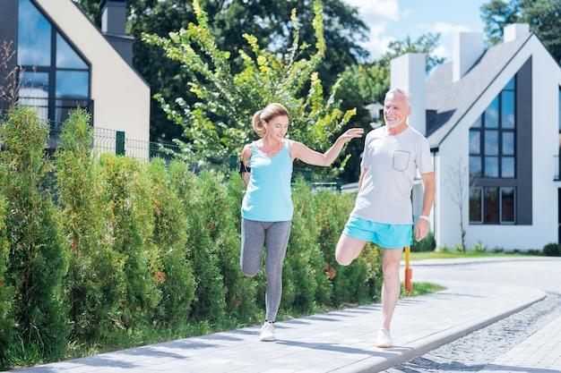 Morgenlauf. bärtiger reifer mann, der sich seiner schönen blonden, schlanken frau anschließt, während er morgens zusammen rennt
