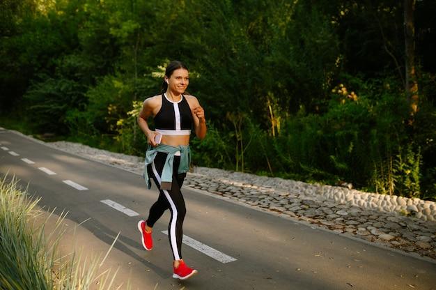 Morgenlauf, frau beim training im sommerpark. die läuferin treibt an einem sonnigen tag sport