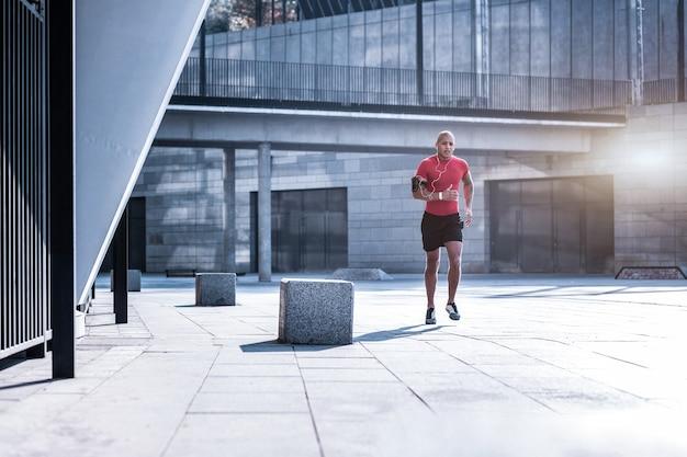 Morgenlauf. hübscher athletischer mann, der musik in den kopfhörern beim laufen in der stadt hört