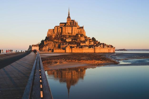 Morgenlicht auf dem mont saint michel und seinem spiegelbild in der normandie