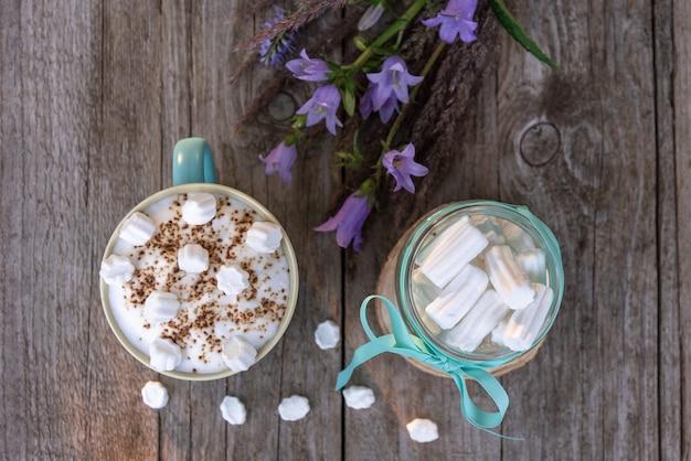 Morgenmokka mit marshmallows auf einem holztisch mit blumen.