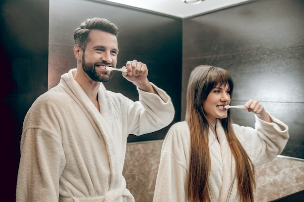 Morgenprozeduren. junges paar in bademänteln, die zähne zusammen putzen