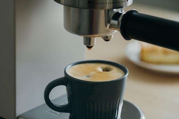 Morgenritual beim frühstück mit eingießen von kaffee aus der kaffeemaschine espressotropfen tropfen
