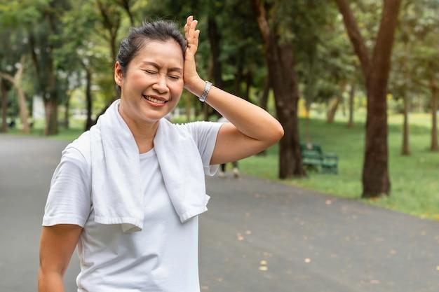 Morgens asiatische kopfschmerzen der seniorfrau während der übung am park.