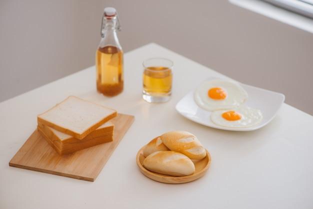 Morgens frühstück mit glas tee, toast, spiegelei und brot auf dem tisch