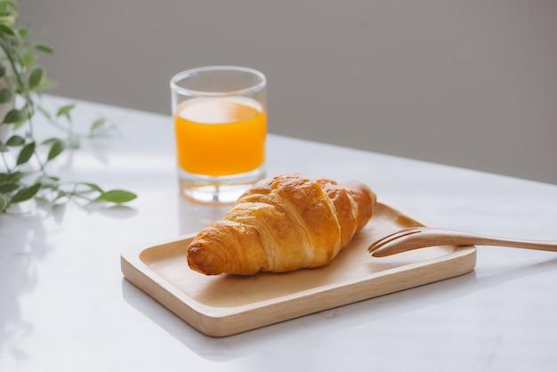 Morgens frühstück mit orangensaft und croissant auf dem tisch
